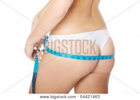 Female's buttocks with measuring tape. Isolated on white.