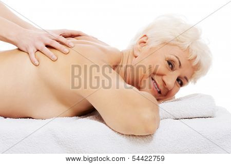 An old woman is having a massage. Spa concept.  Over white.