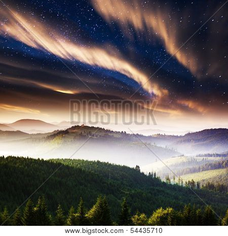The Milky Way over the mountains landscape. Dramatic overcast sky. Carpathian, Ukraine, Europe. Beauty world.