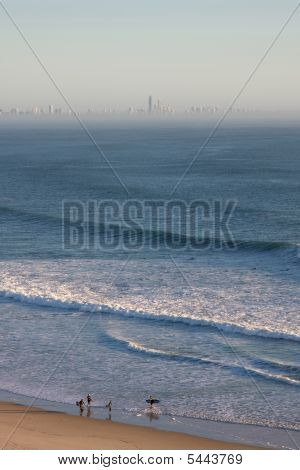 Surfers Walking Along Beach, With Surfer's Paradise On The Horizon
