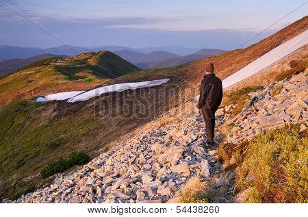 Spring landscape with man tourist on a mountain trail. Carpathians, Ukraine, Europe.