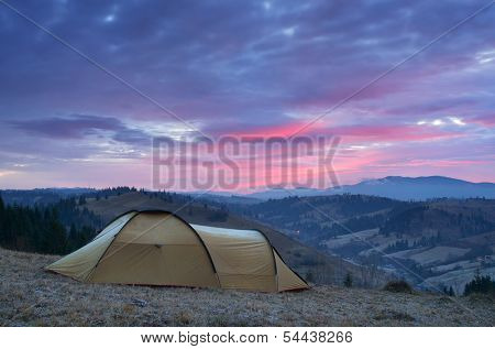 Morning landscape with a tent on the hill. Dawn with hoar-frost on the tent. Camping in the mountains. Carpathians, Ukraine, Europe
