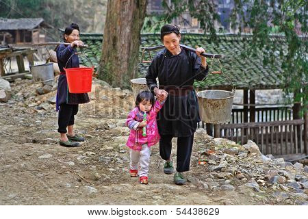 Asian Goes Fetch Water From Bucket On Yoke And Child.