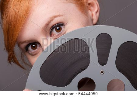 Attractive Redhead Looking Over Film Reel
