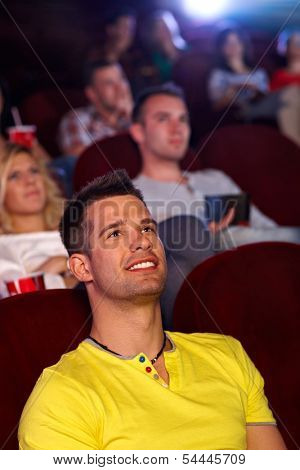 Young man sitting in multiplex movie theater, watching movie, smiling.