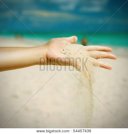 Coral white sand strewing from hand