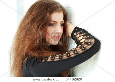 Closeup portrait of a pensive woman leaning at the brick wall