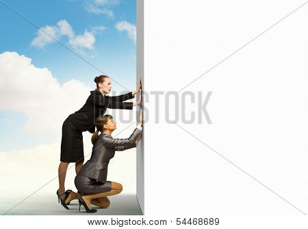Two businesswoman pushing blank white banner. Place for text