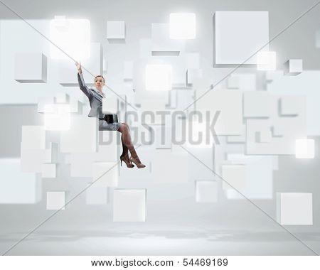 Image of elegant businesswoman sitting on white cube touching media button