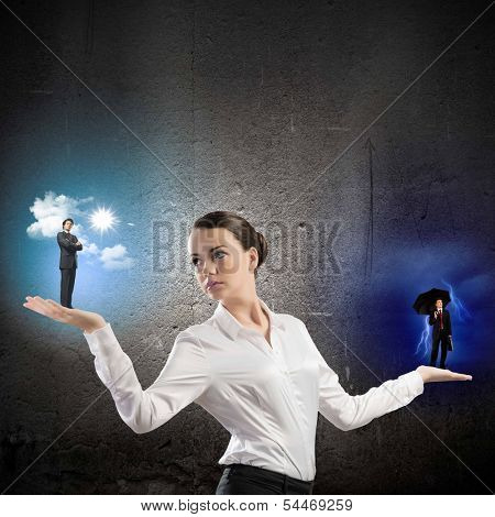 Image of businesswoman holding business persons in miniature on palms