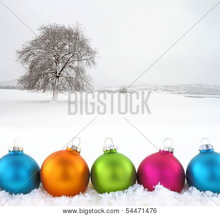 Colorful Christmas balls with snowfield as background