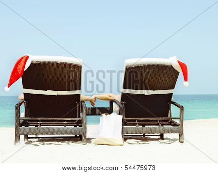 Christmas Card Or Background - Couple In Sunloungers With Santa Hats Standing On Beautiful Tropical