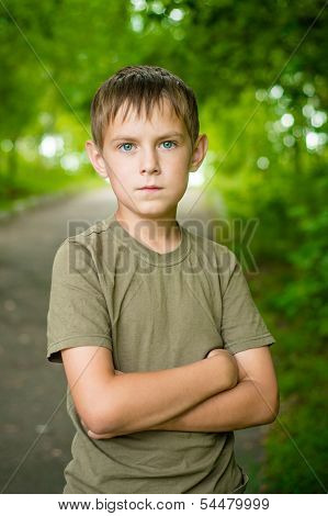 Close-up Portrait Of Serious Little Boy With Folded Hands Outdoors