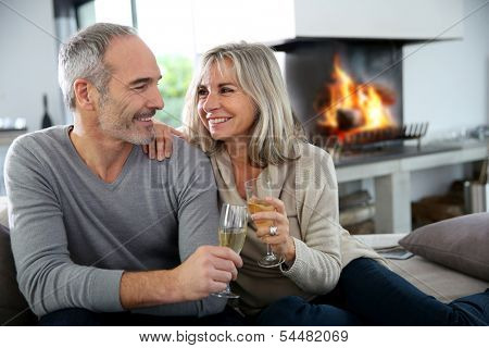 Happy senior couple enjoying glass of champagne