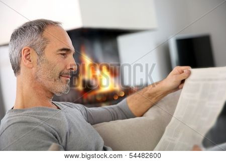 Mature man relaxing by fireplace with newspaper