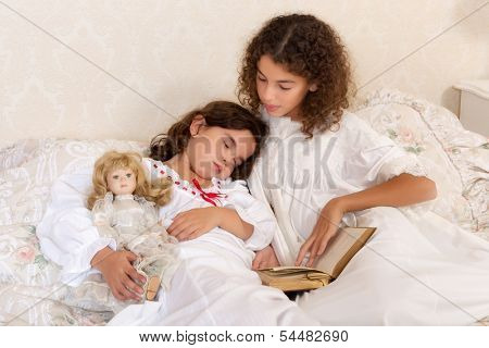 Vintage girl in bed reading a bedtime story to her little sister