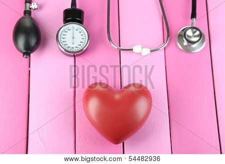 Tonometer, stethoscope and heart on wooden table close-up