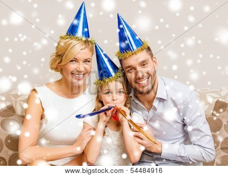 celebration, family, holidays and birthday concept - three smiling women wearing blue hats and blowing favor horns