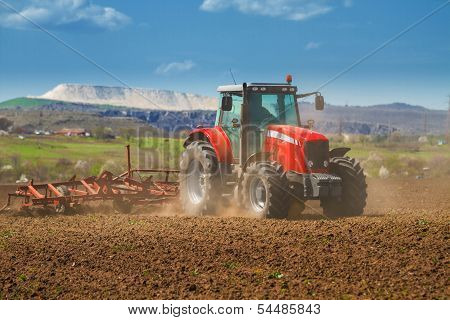 Brand New Red Tractor On The Field Working On Land