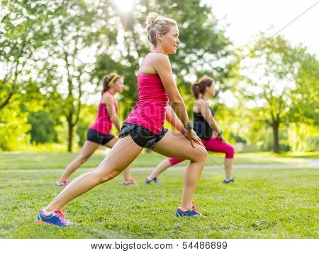 Jogging coach streching with clients