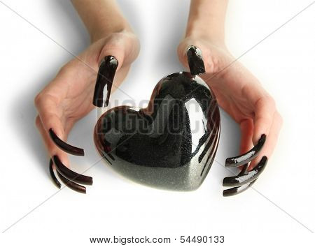 Hands with scary manicure holding black heart , isolated on white
