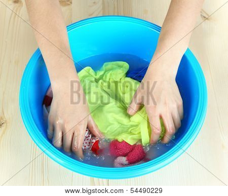Hand washing in plastic bowl on wooden table close-up