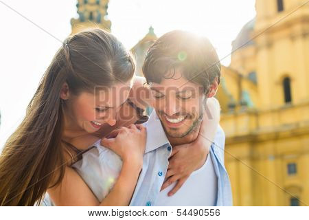 Man and woman or young couple making trip as tourists in city of Munich at the Odeon Church