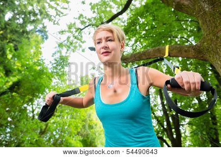 Young woman exercising with suspension trainer sling in City Park under summer trees for sport fitness