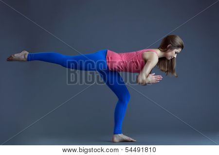 Studio shot of pretty woman doing yoga exercises