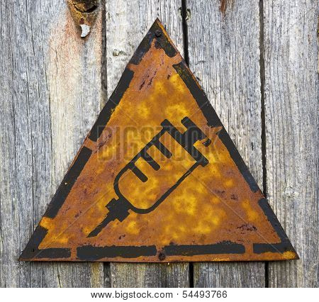 Syringe Icon on Rusty Warning Sign.