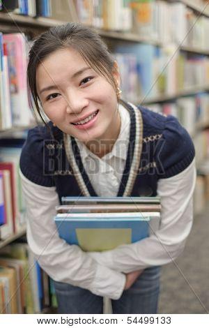 Young Student Holding Books Near Bookshelf