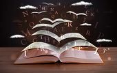 picture of hardcover book  - Pages and glowing letters flying out of a book on wooden deck - JPG