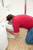 Man kneeling down in the bathroom, vomiting into the toilet.