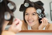 Woman In Hair Curlers Applying Eye Makeup