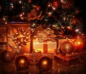 Many different gift boxes wrapped in shiny golden paper under decorated Christmas tree, Christmastim