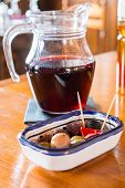 foto of sangria  - Sangria pitcher with plate of small tasty snacks on a table - JPG