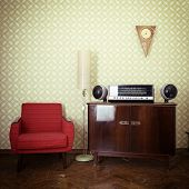Vintage room with wallpaper, old fashioned armchair, retro player, loudspeakers, clocks and standart