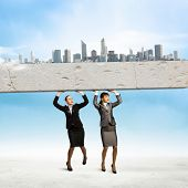 Image of two businesswomen holding stone above head. Partnership and cohesion