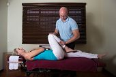 foto of chiropractor  - Chiropractor working with female leg and muscles - JPG