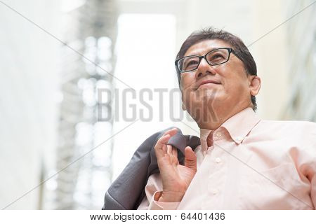 Portrait of 60s Asian Chinese CEO boss smiling and looking away. Senior male businessman, real modern office building as background.