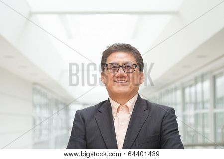Portrait of 60s Asian Chinese CEO boss smiling. Senior male businessman, real modern office building as background.