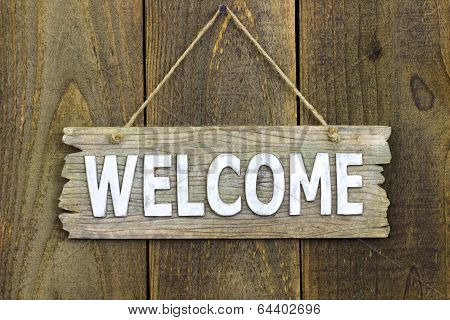 Wood welcome sign hanging on rustic door
