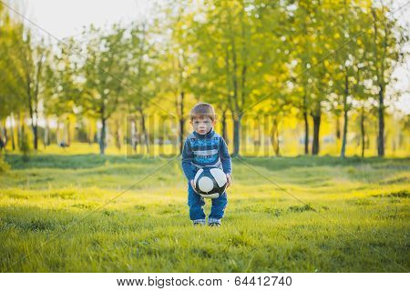 funny boy is kicking ball in the field