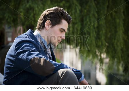 Sad, Worried Young Man Sitting Outdoor In Town