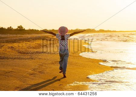 Happy active child splashing and playing in sea.