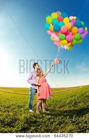 Young healthy beauty pregnant woman with her husband and balloons outdoors. A Men  and girl with a tummy on the grass. Enjoyed by nature. Couple in love waiting for baby