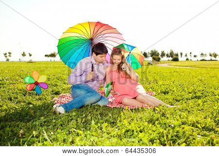 Young healthy beauty pregnant woman with her husband and rainbow umbrellas  outdoors. A Men  and girl with a tummy on the grass. Enjoyed by nature. Couple in love waiting for baby