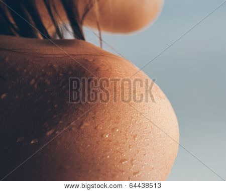 Close up texture of the wet shoulder of a young woman showing skin detail and the way the water condenses and beads on the surface of the skin against a sunny blue summer sky