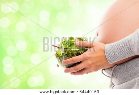 A young and pregnant woman with a fresh green salad.