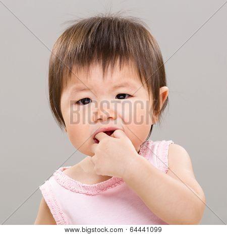Little girl bite her finger